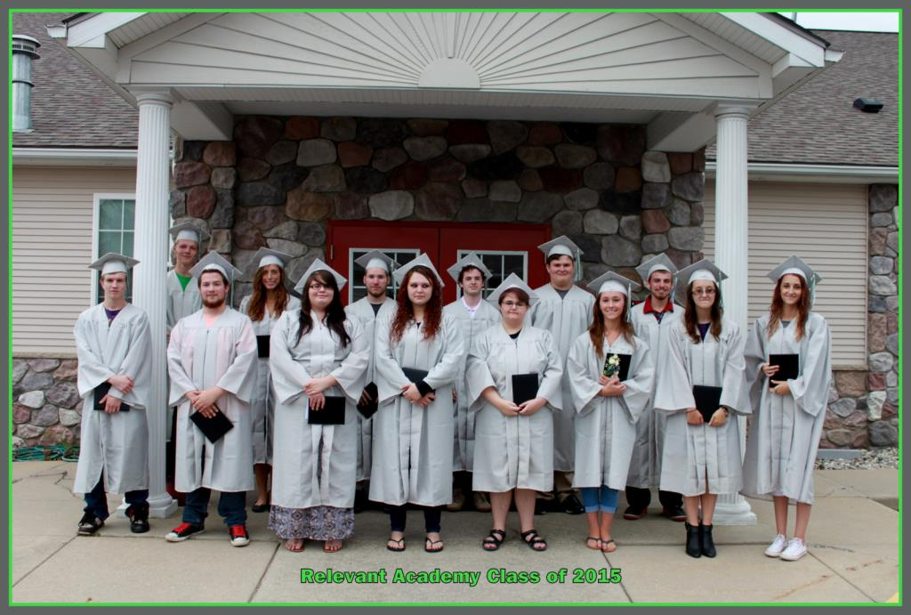 2015 Graduation Students in front of building with caps and gowns on holding diplomas